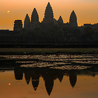 Lake reflection of the famous ancient Angkor Wat temple, with the rising sun in a foggy, orange sky, in Siem Reap, Cambodia Southeast Asia