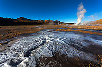 Ice and steam on El Tatio, largest geyser field in Southern Hemisphere, highest in the world (4320m), with sunrise on Atacama Desert mountains, Chile