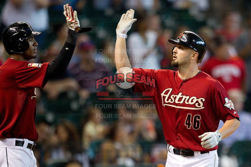 Houston Astros first baseman Scott Moore #46 is greeted at the pate by teammate Jimmy Paredes after hitting a home run in the third inning of the Major League baseball game against the Philadelphia Phillies on September 16th, 2012 at Minute Maid Park in Houston, Texas. The Astros defeated the Phillies 7-6. (Andrew Woolley/Four Seam Images).