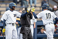 Michigan Wolverines outfielder Christian Bullock (5) greets teammate Blake Nelson (10) after he scored against the Rutgers Scarlet Knights on April 27, 2019 in the NCAA baseball game at Ray Fisher Stadium in Ann Arbor, Michigan. Michigan defeated Rutgers 10-1. (Andrew Woolley/Four Seam Images)