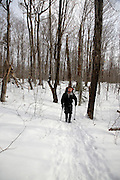 Hiker on Mount Tecumseh Trail during the winter months in the White Mountains, New Hampshire USA.