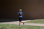 Young Caucasian woman running along the a bike path in Denver, Colorado. .  John offers private photo tours in Denver, Boulder and throughout Colorado. Year-round Colorado photo tours.