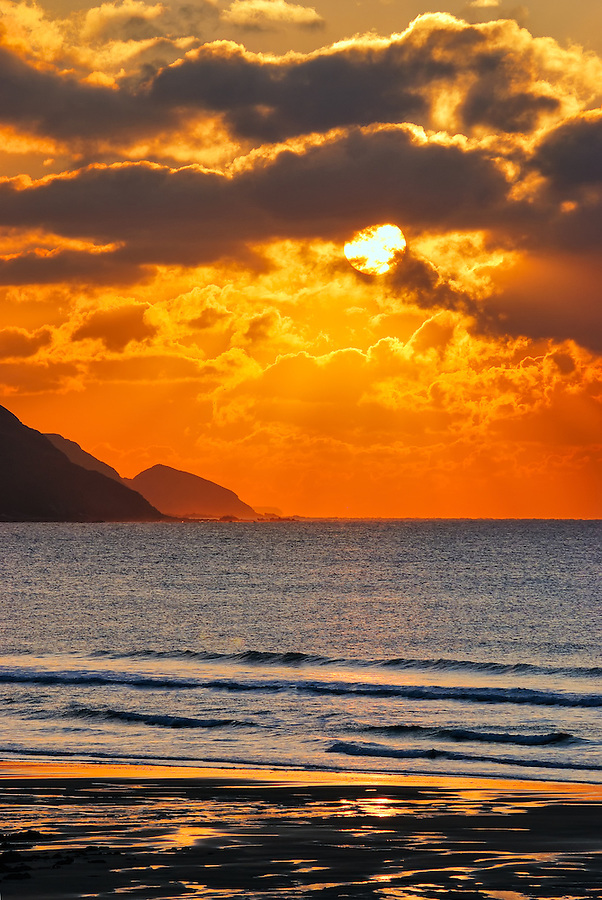 Widemouth Bay, just south of Bude, is one of the very best places on the North Cornwall coastline to catch, and photograph, memorable sunsets. On this particularly evening the sky turned a vibrant orange well before the sun had got anywhere near the horizon. The bump on the left is Cambeak at Crackington