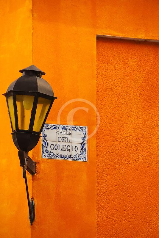 Uruguay, Colonia de Sacramento, Single lamp and sign on orange wall, historic district