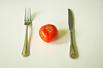 Tomato, knife and fork stillife.