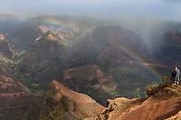 A woman and a man enjoy the overview of Wamea Canyon with a rainbow, Kaua'i.