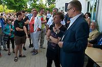 """Auf einer Buergerversammlung mit ca. 500 Teilnehmern im Berliner Plattenbaubezirk Hellersdorf entlud sich am Dienstag den 9. Juli 2013 der blanker Rassismus gegen eine geplante Unterkunft fuer syrische Buergerkriegsfluechlinge. Etwa 2/3 Anwesende aeusserten, es solle """"zuerst was fuer Deutsche getan werden"""", """"das Heim anzuenden"""", """"Wer sein Heimatland verlaesst ist ein Verraeter"""", """"Wer denkt an unsere Kinder"""" und aehnliche Parolen gegen das Fluechtlingsheim. Veranstaltungsteilnehmer, die Verstaendnis fuer die Buergerkriegsfluechtlinge aeusserten, wurden niedergebruellt.<br />Im Bild: Der Lebnsgefaehrtin des Berliner NPD-Fuehrers Sebastian Schmidtke, Maria Fank, wird die Moeglichkeit gegeben, zu den Veranstaltungsteilnehmern zu reden.<br />Als Veranstaltungsteilnehmerin mit schwarzem T-Shirt und verschraenkten Armen in der zweiten Reihe stehend: Daniela Froehlich, ehemalige Anti-Antifa-Fotografin und Aktivistin. <br />9.7.2013, Berlin<br />Copyright: Christian-Ditsch.de<br />[Inhaltsveraendernde Manipulation des Fotos nur nach ausdruecklicher Genehmigung des Fotografen. Vereinbarungen ueber Abtretung von Persoenlichkeitsrechten/Model Release der abgebildeten Person/Personen liegen nicht vor. NO MODEL RELEASE! Don't publish without copyright Christian-Ditsch.de, Veroeffentlichung nur mit Fotografennennung, sowie gegen Honorar, MwSt. und Beleg. Konto:, I N G - D i B a, IBAN DE58500105175400192269, BIC INGDDEFFXXX, Kontakt: post@christian-ditsch.de<br />Urhebervermerk wird gemaess Paragraph 13 UHG verlangt.]"""