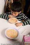 Preschool Headstart 3-5 year olds boy eating breakfast cereal with milk vertical