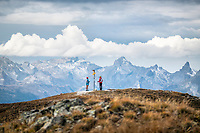Two runners stand looking at a trail sign while on the Via Valais, a multi-day trail running tour connecting Verbier with Zermatt, Switzerland.