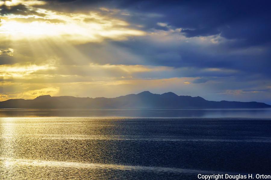 A rainstorm begins.  Great Salt Lake, Utah.  Viewed from Great Salt Lake State Park, Salt lake City area.  Sailing regatta on calm waters.  Anelope Island in background.