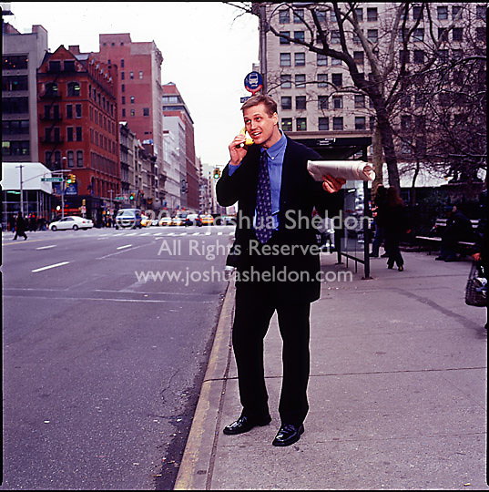 Man in suit standing on sidewalk holding a newspaper and talking into a banana