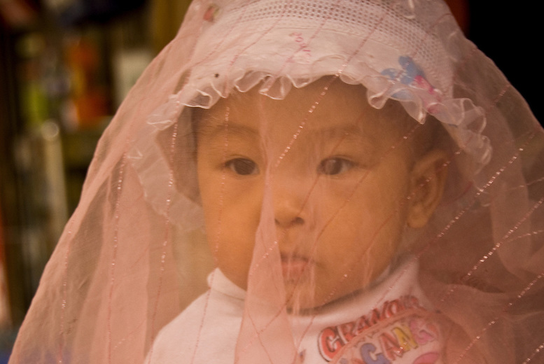 A small child wears a veil to protect her from the sun, bugs and diesel fumes in Hanoi, Vietnam.  Many Vietnamese wear face shields to protect themselves from the motorbike and car fumes. Emissions are  unregulated and produce a significant amount of air pollution in the cities.