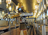 Samurai robot waiter sliding in the restaurant to serve food in the Hajime Restaurant, out-skirts of Bangkok, Thailand. Hajime is a Japanese restaurant in Thailand, has samurai style robot serving food to the diners and even do a dance session to entertain guests. This robot are made in Japan and costed about 86,600,000 yen (1,063,717USD). Customers order food from touch panel and Samurai robot will bring ordered food to their table.<br />