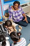 Education preschool teacher observing and encouraging in background as two girls and a boy build with blocks