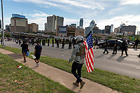 AUSTIN, TEXAS - MAY 30, a man wearing a bullet proof vest and helmet holds an American flag as Austin Police Department officers line the I-35 service road on May 30, 2020 in Austin, Texas.<br />