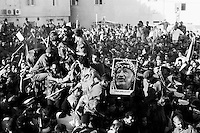 Pile on top of car carrying Yasser Arafat's body the day of the funeral.