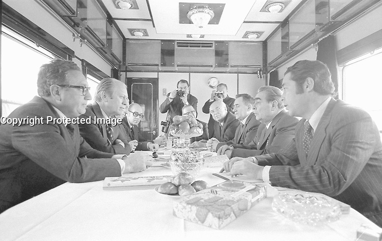 Photograph of President Gerald Ford, Secretary of State Henry Kissinger and other U.S. Representatives meeting with General Secretary Brezhnev, Foreign Secretary Gromyko, Ambassador Dobrynin, and the others aboard a Russian train headed for Vladivostok. NOV 1974
