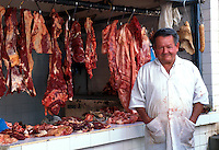 A smiling Columbian butcher vendor in front of his shop. Colombia.