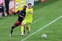 NASHVILLE, TN - SEPTEMBER 23: Alex Muyl #29 of Nashville SC knocks Oniel Fisher #91 of DC United off of the ball during a game between D.C. United and Nashville SC at Nissan Stadium on September 23, 2020 in Nashville, Tennessee.