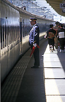 "A station controller waves his flag as women wearing kimonos pass a Shinkansen ""bullet train"" in Tokyo, Japan. The Bullet train could be thought of as the world's first speed train. Services started in 1964 with speeds at 210km/h or 131mph, the fastest trains went at the time, and many countries stills have no trains running at this speed."