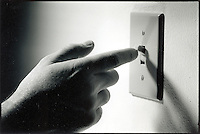 Hand turning on light switch on wall.