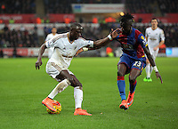 (L-R) Modou Barrow of Swansea is closely marked by Pape Souare of Crystal Palace during the Barclays Premier League match between Swansea City and Crystal Palace at the Liberty Stadium, Swansea on February 06 2016