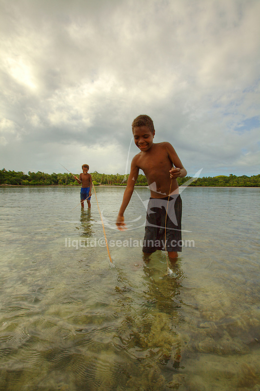 Children spare fishing with a trident at Hessessai Bay at PanaTinai (Panatinane)island in the Louisiade Archipelago in Milne Bay Province, Papua New Guinea. The island has an area of 78 km2..The Louisiade Archipelago is a string of ten larger volcanic islands frequently fringed by coral reefs, and 90 smaller coral islands located 200 km southeast of New Guinea, stretching over more than 160 km and spread over an ocean area of 26,000 km? between the Solomon Sea to the north and the Coral Sea to the south. The aggregate land area of the islands is about 1,790 km? (690 square miles), with Vanatinai (formerly Sudest or Tagula as named by European claimants on Western maps) being the largest..Sideia Island and Basilaki Island lie closest to New Guinea, while Misima, Vanatinai, and Rossel islands lie further east..The archipelago is divided into the Local Level Government (LLG) areas Louisiade Rural (western part, with Misima), and Yaleyamba (western part, with Rossell and Tagula islands. The LLG areas are part of Samarai-Murua District district of Milne Bay. The seat of the Louisiade Rural LLG is Bwagaoia on Misima Island, the population center of the archipelago.PanaTinai (Panatinane) is an island in the Louisiade Archipelago in Milne Bay Province, Papua New Guinea. The island has an area of 78 km2..The Louisiade Archipelago is a string of ten larger volcanic islands frequently fringed by coral reefs, and 90 smaller coral islands located 200 km southeast of New Guinea, stretching over more than 160 km and spread over an ocean area of 26,000 km? between the Solomon Sea to the north and the Coral Sea to the south. The aggregate land area of the islands is about 1,790 km? (690 square miles), with Vanatinai (formerly Sudest or Tagula as named by European claimants on Western maps) being the largest..Sideia Island and Basilaki Island lie closest to New Guinea, while Misima, Vanatinai, and Rossel islands lie further east..The archipelago is divided into the Local Level Govern