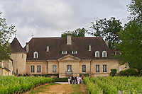 A group of visiting wine tasters in the vineyard in front of the chateau building Chateau Bouscaut Cru Classe Cadaujac Graves Pessac Leognan Bordeaux Gironde Aquitaine France