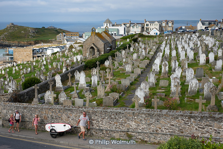 Family with a surfboard on their way from the beach,  Barnoon cemetery, St.Ives, Cornwall.