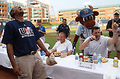 """On-field annoucer Jatovi McDuffie laughs as Mark Thomas talks to the crowd during the Bright Leaf Hotdog Eating Contest. """"I've been training for this all my life,"""" said Thomas. Photo by Al Drago."""