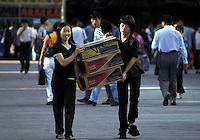 Two women hold Sony and Panasonic VCD players on the street in Shenzhen, China..