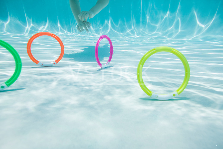 USA Florida, St. Pete Beach, Underwater shot of colorful circles on swimming pool floor, girl's (8-9) hands in background