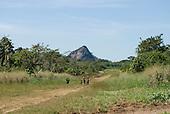 Pará State, Brazil. Aldeia Kendjam (Kayapo). Sacred rock rising from the forest floor, women and children returning from the river.