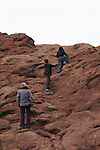 Mother watching her two sons scramble in Arches National Park, Moab, Utah, USA. .  John offers private photo tours in Arches National Park and throughout Utah and Colorado. Year-round.