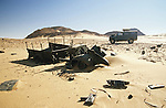 Africa, Libya, Fezzan. Land Rover Defender 110 behind the remains of one of three LRDG Chevrolet trucks in a valley of the Gebel Sherif mountains southwest of Kufra. During Second World War on January 31 1941 the Long Range Desert Group was attacked by the Italian Compagnie Sahariane. Libyen 1999/2000.<br /> <br />  --- No releases available. Automotive trademarks are the property of the trademark holder, authorization may be needed for some uses.<br /> <br />  --- INFO: The Long Range Desert Group (LRDG) was a reconnaissance and raiding unit of the British Army during the Second World War. Originally called the Long Range Patrol Unit (LRP), the unit was founded in Egypt in June 1940 by Major Ralph A. Bagnold. Bagnold was assisted by Captain Patrick Clayton and Captain William Shaw. At first the majority of the men were from New Zealand, but they were soon joined by Rhodesian and British volunteers, whereupon new sub-units were formed and the name was changed to the better-known Long Range Desert Group (LRDG).<br /> <br /> The LRDG vehicles were mainly two wheel drive, chosen because they were lighter and used less fuel than four wheel drive. They were stripped of all non-essentials, including doors, windscreens and roofs. They were fitted with a bigger radiator, a condenser system, built up leaf springs for the harsh terrain, wide, low pressure desert tyres, sand mats and channels etc.  Initially the LRDG patrols were equipped with one CMP Ford 15 cwt F15 truck for the commander, while the rest of the patrol used up to 10 Chevrolet 30 cwt WB trucks.<br /> <br /> On 31 January 1941 'T' Patrol commanded by Captain Patrick Clayton was attacked by the Compagnia Autosahariana di Cufra, an Italian unit similar to the LRDG, in the Gebel Sherif valley south of Cufra, Libya. The LRDG had one man killed and three men captured, and three of the eleven trucks were destroyed during the battle. The Italians losses were five killed and three wounded, and one truck was abandoned.
