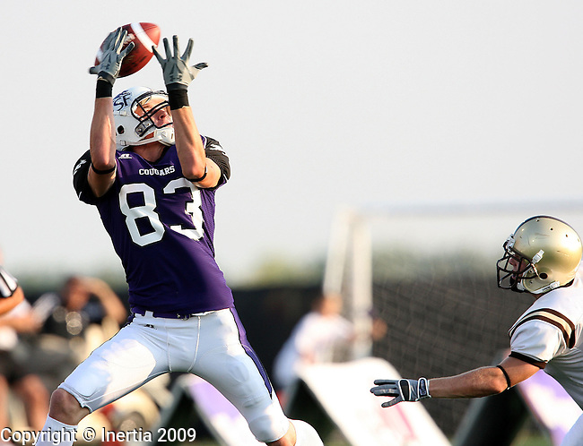 SIOUX FALLS, SD - SEPTEMBER 5:  Jon Ryan #83 of the University of Sioux Falls hauls in a pass in front of a Nebraska Wesleyan defender on a key third down play in the first quarter of their game Saturday evening at the USF Sports Complex. (Photo by Dave Eggen/Inertia).
