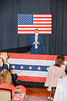 A Secret Service officer stands in front of an American flag by the stage before Eric Trump, son of US president Donald Trump, holds a Make America Great Again! campaign rally at the DoubleTree by Hilton Manchester Downtown in Manchester, New Hampshire, on Mon., Oct. 19, 2020. The audience chairs are distanced to follow safety protocols during the ongoing Coronavirus (COVID-19) global pandemic, just a few weeks after Donald Trump himself contracted the disease, though many other Trump campaign events are lax about COVID safety protocols.