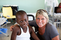 Devastation after the January 12, 2010 earthquake. Alison with Peterson the orphan who had his leg amputated, St. Damien's Hospital.