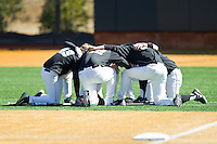 Several of the Wake Forest Demon Deacons players huddle up in right field prior to the game against the Youngstown State Penguins at Wake Forest Baseball Park on February 24, 2013 in Winston-Salem, North Carolina.  The Demon Deacons defeated the Penguins 6-5.  (Brian Westerholt/Four Seam Images)