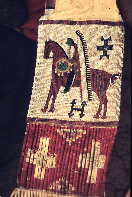 Beaded Pawnee pipe bag made from deer hide and decorated with a design of a warrior on horseback. The bottom of bag is decorated with dyed quillwork wrapped around long fringe