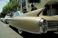 The rear fender and tail fin of a 1960 Cadillac, parked on a street. Chrome, style, automobiles, vintage, ornamental functional design detail. New Jersey.