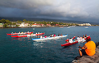 A coach gives tips to outrigger canoe paddlers during club practice at Kailua Bay on the Big Island.