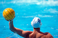 A male waterpolo player holds the ball in hand.