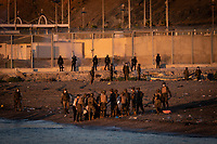 CEUTA, SPAIN ‐ MAY 19: A group of riot police fires tear gas at the border fence between Spain and Morocco to prevent more people from approaching to try to cross it while the Spanish military intercepts a group of migrants who were swimming across the border on May 19, 2021 in Ceuta, Spain.  After a diplomatic conflict between Spain and Morocco, thousands of migrants who have taken advantage of the little Moroccan police activity on the border to cross it mainly by swimming, which has caused a migration crisis with the entry of more than 8000 migrants from the African country. (Photo by Joan Amengual/VIEWpress )