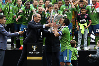 SEATTLE, WA - NOVEMBER 10: MLS Commissioner Don Garber presents the Philip F. Anschutz Trophy to Seattle Sounders FC team captain Nicolas Lodeiro #10 who then kisses it during a game between Toronto FC and Seattle Sounders FC at CenturyLink Field on November 10, 2019 in Seattle, Washington.