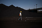 An Indian workers is seen at the coal deposits of Adani Power at the Mundra Port in Gujarat, India.