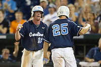North Carolina third baseman Colin Moran (18) celebrates with teammate Cody Stubbs (25) after he scored during Game 10 of the 2013 Men's College World Series against the North Carolina State Wolfpack on June 20, 2013 at TD Ameritrade Park in Omaha, Nebraska. The Tar Heels defeated the Wolfpack 7-0, eliminating North Carolina State from the tournament. (Andrew Woolley/Four Seam Images)