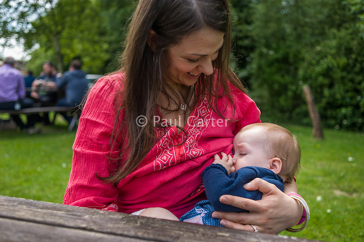 A mother breastfeeding her baby in a pub garden.<br /> <br /> Hampshire, England, UK<br /> 19/06/2013<br /> <br /> © Paul Carter / wdiip.co.uk