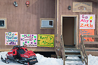 Musher welcome signs on the washeteria building at the Shageluk checkpoint during Iditarod 2009