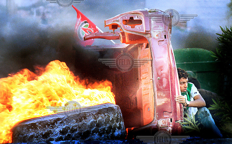 © Ami Vitale / Panos Pictures..A Palestinian protester hides from Israeli soldiers behind a burning tire and car as protests flared again near the West Bank town of Ramallah Wednesday, October 11, 2000.